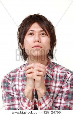 portrait of man folding his hands in prayer