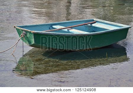 Small green rowboat moored at the shore of the lake