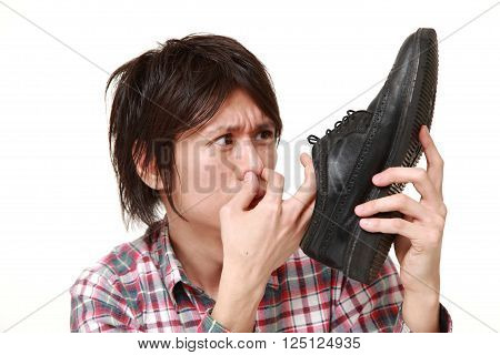 portrait of Young Japanese man smelling his shoes