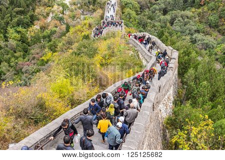 Beijing China - October 14 2013: A view of the Great Wall in Beijing China. The Visitors are both locals and foreigners. They walk up and down the steep stairs on a cloudy day.