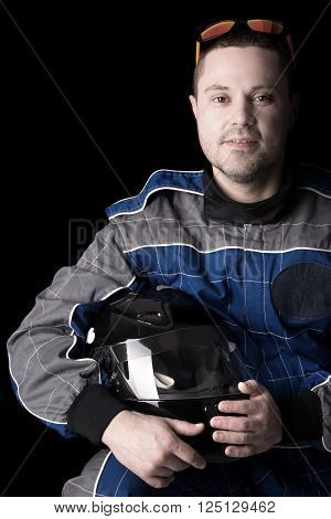 Racing driver posing with helmet isolated in a dark background