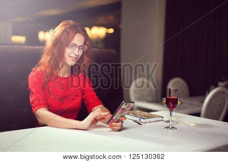 Beautiful girl talking on the phone in a cafe and drink wine,girl in the interior.