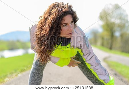 Smiling attractive woman wearing a luminous high visibility jacket working out on a rural road close up