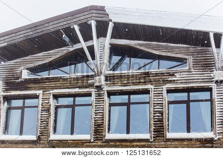 Wooden facade with windows at hoarfrost snowy weather