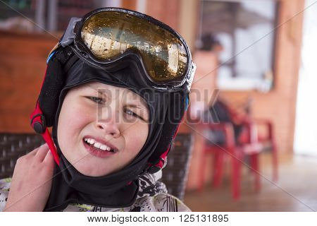Portrait of a boy in ski helmet and protective glasses with neck pain