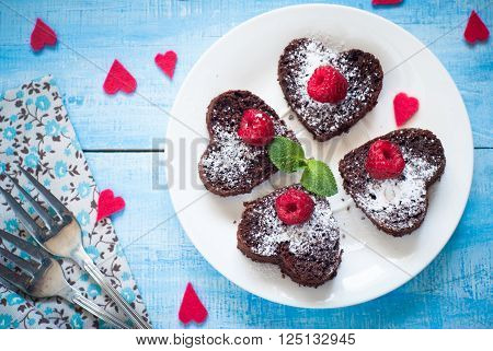 Brownie heart-shaped decorated with berries. Chocolate dessert.