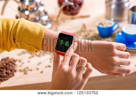Female hands with smart watch showing time with alternative coffee stuff on the background