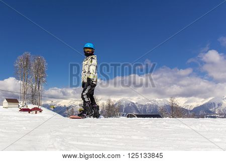 Portrait of young snowboarder in protective ski helmet and glasses