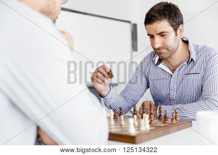 Portrait of two young man playing chess