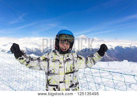 Joyful boy in protective ski helmet on scenery mountain top view background