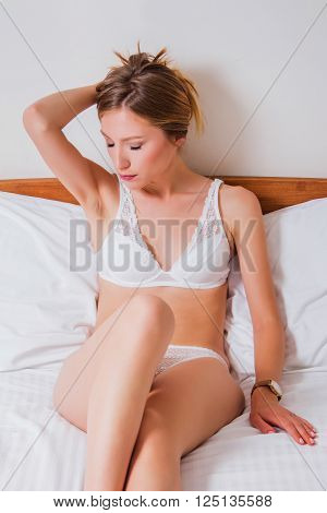 Sexy girl in white lace underwear lying on the bed, eyes closed, emotive expression, boudoir beauty concept