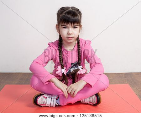 Girl In  Pink Clothes Is Sitting On The Mat