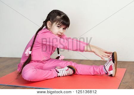 Children. Fitness. A cute little girl in a pink sport suit performing stretching to the foot