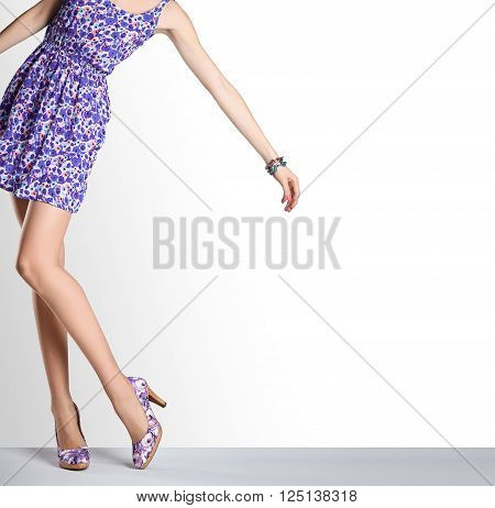 Woman in fashion vintage dress and high heels. Perfect female sexy long legs, stylish purple flower sundress and summer glamour shoes. Unusual creative elegant walking out outfit, people. Copy space
