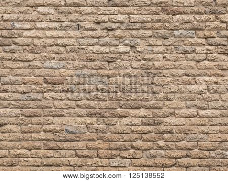 beautiful decorative wall made of light beige natural stone with dents bumps and spots laid like a brick and concrete joints