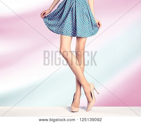 Woman long legs in fashion dress, high heels. Perfect female  sexy legs, stylish blue skirt and summer glamour shoes, colorful abstract background. Unusual creative elegant walking out outfit, people