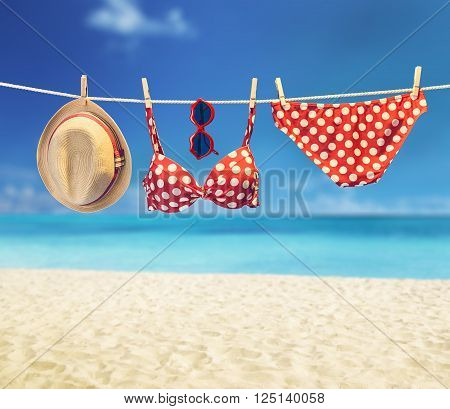 Beach outfit. Summer clothes and accessories stylish set. Fashion swimsuit bikini red polka dots, sunglasses hat.