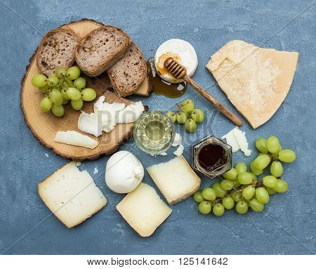 Cheese appetizer selection or wine snack set. Variety of italian cheese, green grapes, bread slices and honey on round wooden board over grey-blue concrete backdrop, top view