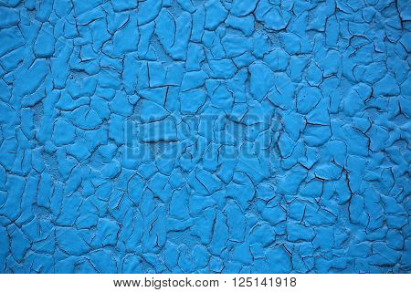 Cracked paint coat layer on iron sheet plate screen aged grungy rough surface with rusty spots damaged on blue background