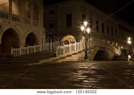 bridge via the Palace channel a lamp and a wall of Doges Palace at night during a rain Venice