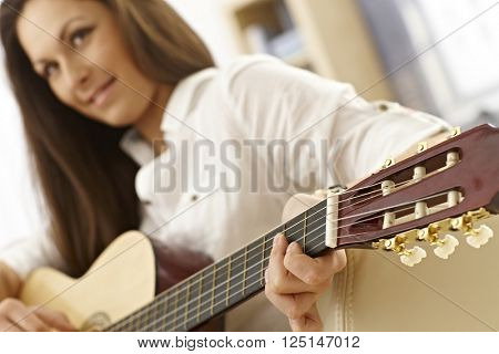 Young female playing guitar. Focus on strings of guitar.
