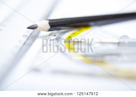 Drawing tools on a paper. Extremely close-up photo with shallow depth of field. Focus on pencil