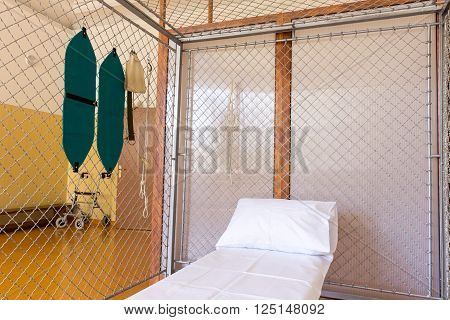 Sofia, Bulgaria - April 7, 2016: A room in a rehabilitation clinic part of a military hospital. A bed in a metal cage.