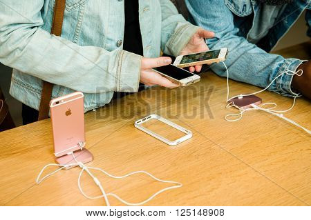 STRASBOURG FRANCE - APR 9 2016: Young friends comparing the new Apple SE and iPhone 4 and iPhone 6S phone during the sales launch of the latest Apple Inc. smartphones at the Apple store in Paris FranceiPhone SE was released on March 31 2016