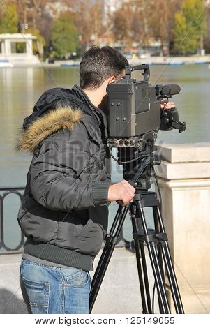 Professional cameraman with video camera in shooting process. Digital media recording