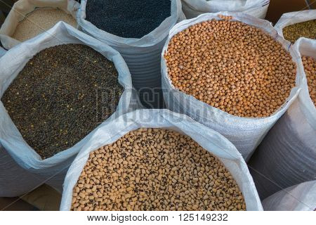 View on different assorted raw legumes in white bags from above. Chick peas beans lentils