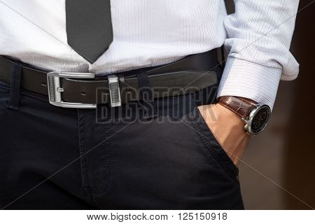 Closeup shot of male waist with hand in pocket dressed in black pants belt grey shirt black tie and watch with brown watch strap