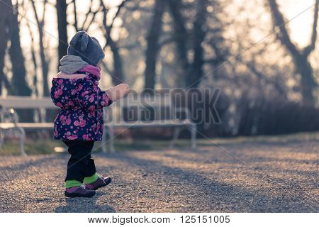 Little baby toddler curiously exploring park outdoors in winter