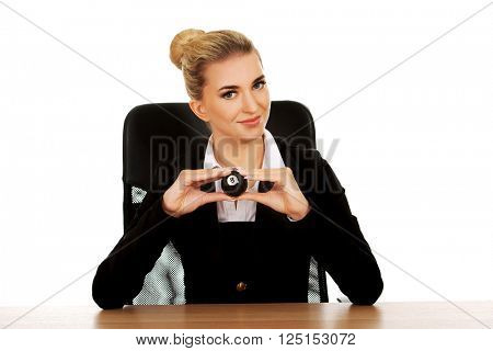 Businesswoman holding eight billiard ball by a desk