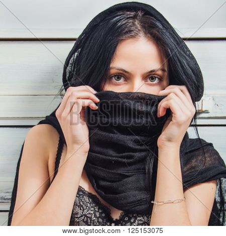 Portrait of beautiful young sexy girl with her face covered with black scarf