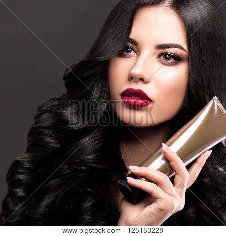 Beautiful brunette model with curls, classic makeup and red lips with a bottle of hair products. The beauty of the face. Portrait shot in the studio on a gray background.