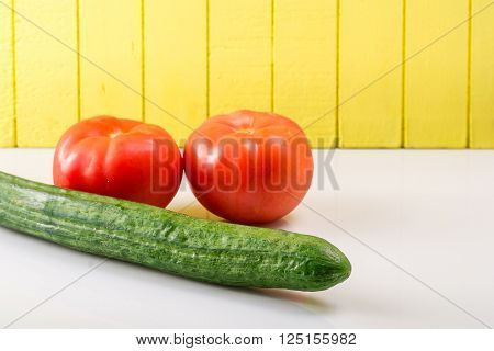 Two ripe tomatoesa nd cucumber against a light background propped up