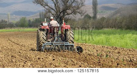 pictureof a man in tractor plowing field in spring