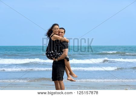Couple enjoying on beach.Young happy interracial couple have fun on beach. Asian womanCaucasian man