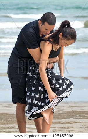 Couple enjoying on beach.Young happy interracial couple looking down together on beach. Asian womanCaucasian man