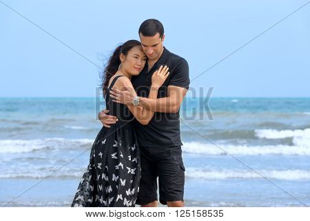 Happy romantic couple on beach.Young happy interracial couple on beach embracing each other. Asian womanCaucasian man
