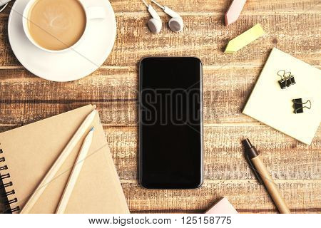 Topview of wooden table with blank phone coffee and office tools. Mock up