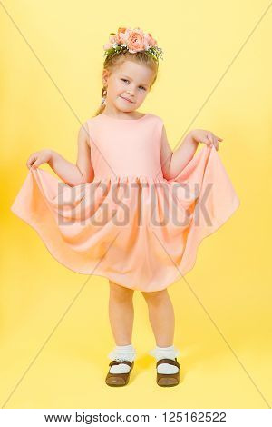 beautiful young pretty girl in beige dress with wreathe on her had in photo studio on yellow background