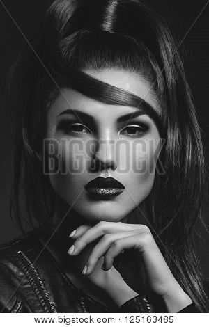 Beautiful young woman with dark red lips and stylish ponytail. Beauty shot. Over black background. Copy space.