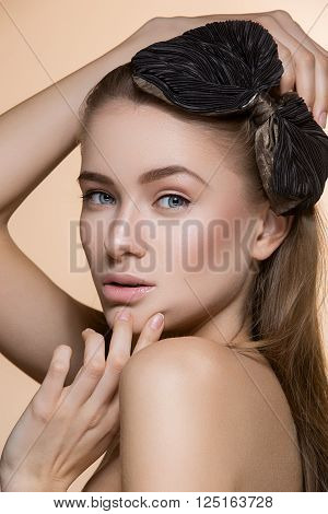 Beautiful young woman with perfect skin and loose hair. Beauty shot. Over background.