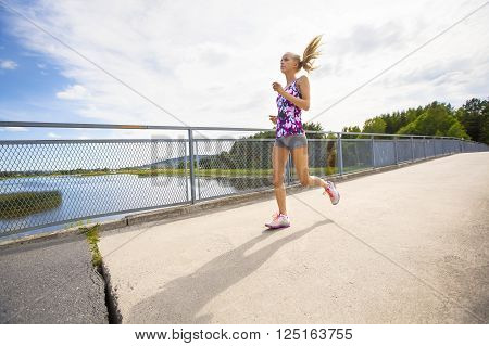 Beautiful and dedicated young slim blonde woman running or jogging on a bridge over a lake.