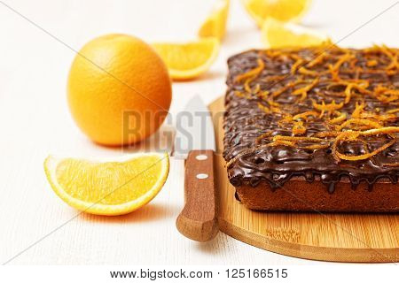 Chocolate and orange cake with orange peel near orange and knife on white wooden background. Shallow focus.