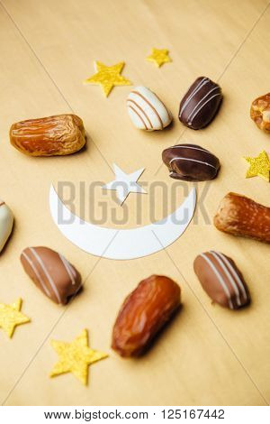 Close up of date chocolates with confetti. Islamic Festive background. Exotic date chocolates.