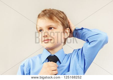 Little funny kid straighten his tie over bright blue shirt