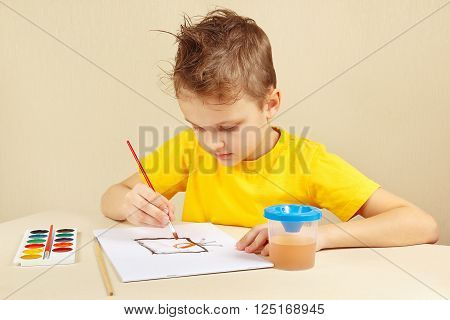 Beginner artist in a yellow shirt painting with watercolors