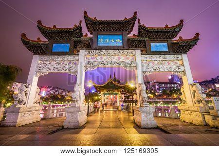GUIYANG, CHINA - JUNE 4, 2014: Tourists pass the historic gate over the Nanming River at night.